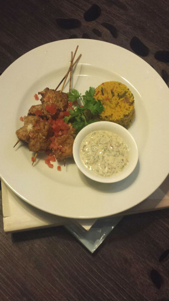 Coconut jerk pork skewers with yellow rice & mint and red onion yogurt